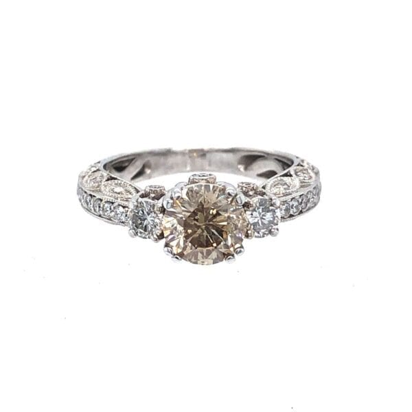 18 karat white gold, vintage inspired, 1.00ct champagne round brilliant cut diamond ring.  The clarity is I1.  The ring is set with 0.50 carat total weight of smaller diamonds.